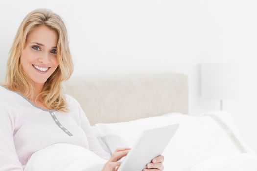Closer shot, Woman in bed with tablet pc in hand, looking up and