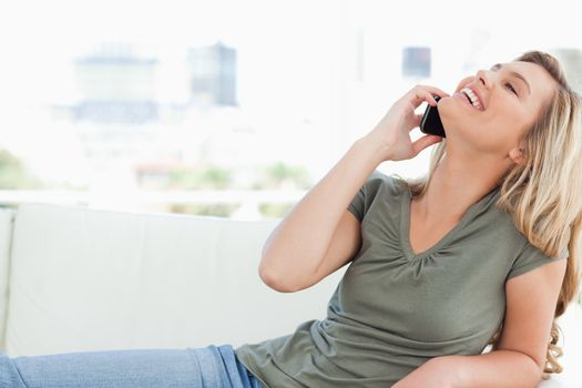 Woman with head raised back and smiling as she makes a call whil