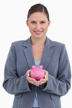 Smiling bank clerk holding piggy bank