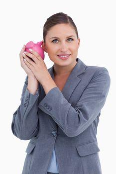 Smiling bank clerk shaking piggy bank