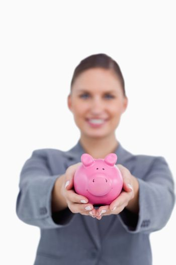 Piggy bank being offered by smiling bank clerk