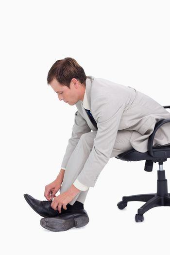 Side view of businessman fastening his shoes