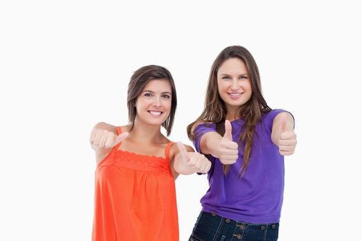 Woman standing up her thumbs turned to the side while her friend
