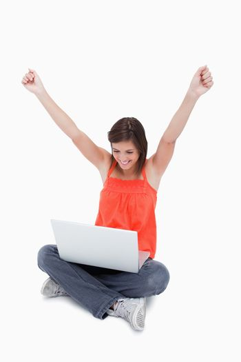 Teenager showing her satisfaction behind her laptop while raisin