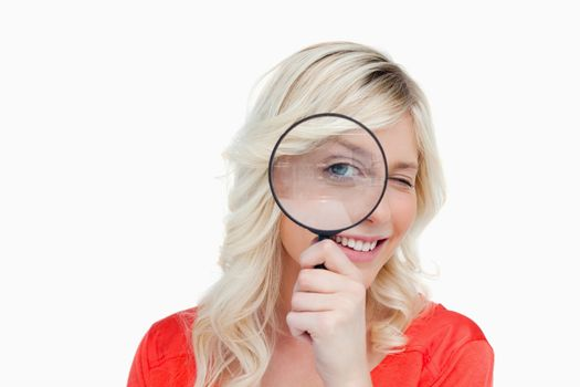 Woman looking through a magnifying glass while blinking an eye