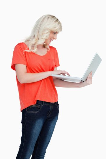 Woman standing upright while using the touchpad of her laptop