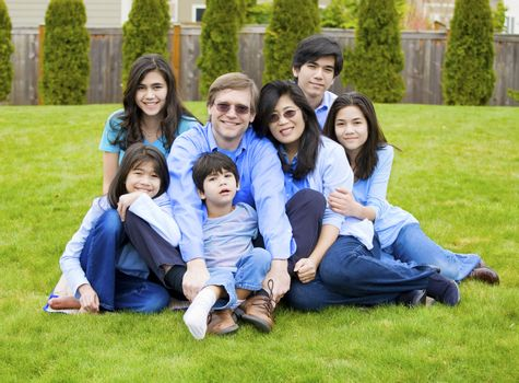 Large family of seven sitting together on lawn, dressed in blue