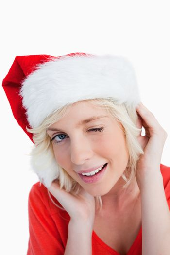 Young woman wearing Christmas clothes while blinking an eye