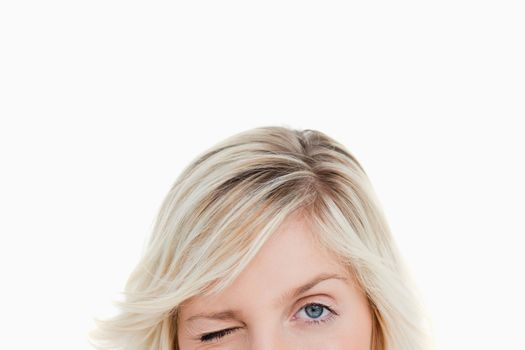 Upper part of the face of a fair-haired woman blinking an eye