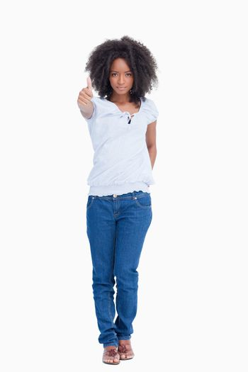 Serious woman standing upright with her thumbs up and a hand on