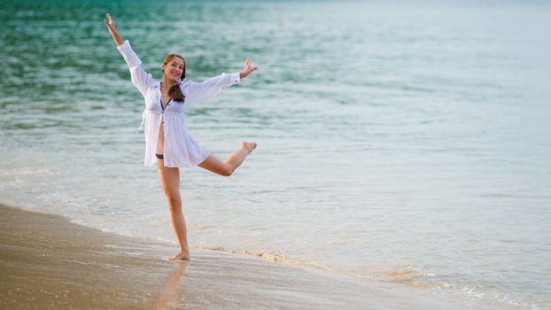 Young woman dancing in the sea