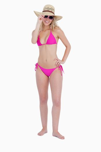 Smiling teenage wearing a pink swimsuit while holding her hat br