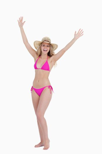 Blonde teenager raising her arms while standing upright
