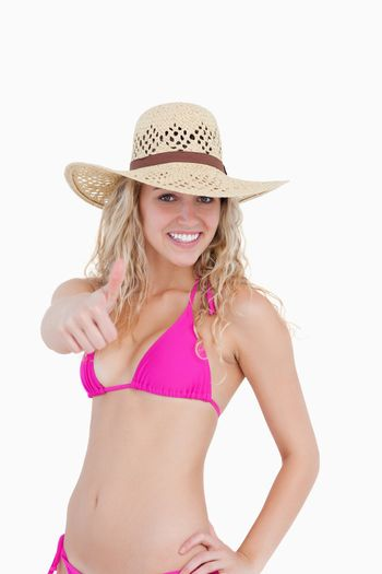 Thin teenager in beachwear showing her thumbs up