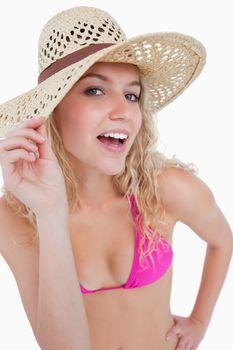 Attractive blonde teenager holding her hat brim