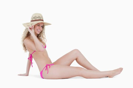 Young blonde woman sitting on the floor while holding her hat br