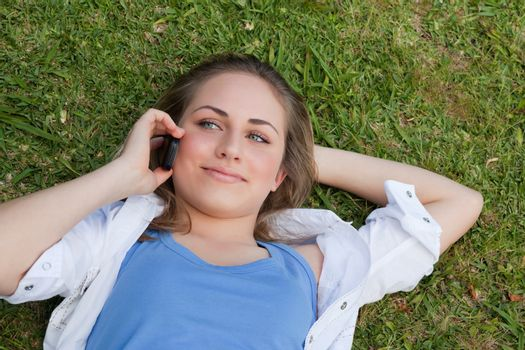 Young relaxed blonde girl lying on her back while talking on the