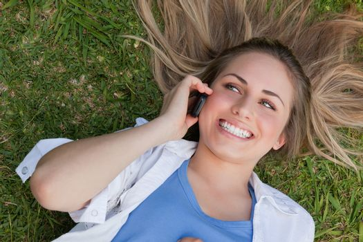Young smiling woman lying on her back while using her cellphone