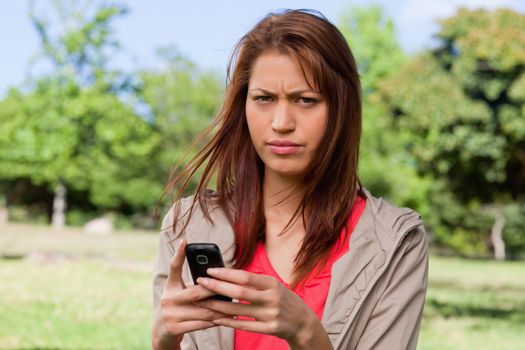 Woman with a stern expression on her face while holding a phone