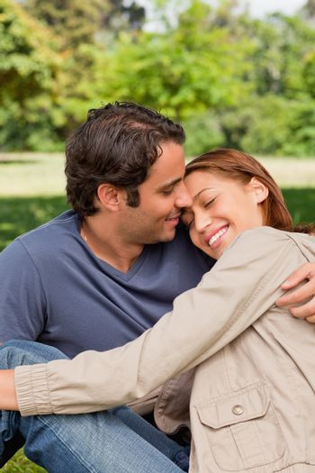 Man smiling as his friend rests her head on his shoulders