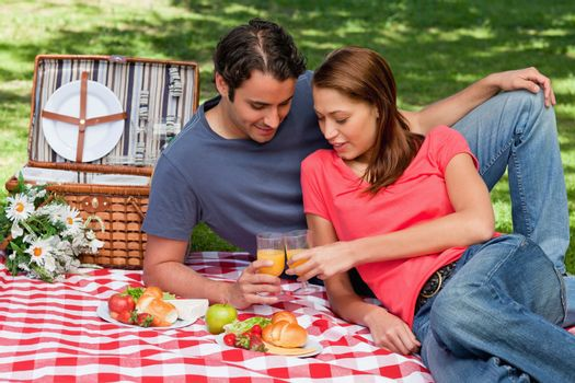 Two friends touching glasses against each other in celebration while lying on a blanket with picnic food