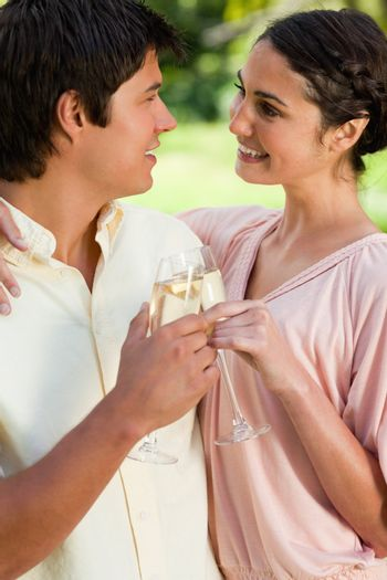 Man and a woman smiling and holding each other while touching glasses of champagne in celebration