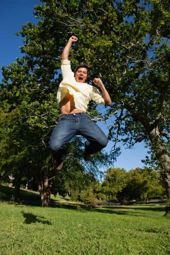 Man looks downwards as he jumps off the ground while raising his arms in celebration in the park