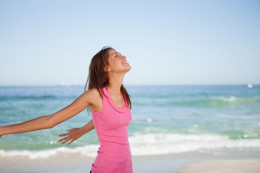Young woman standing upright while sunbathing on the beach
