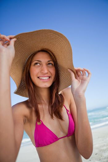 Smiling attractive teenager holding her hat brim in front of the