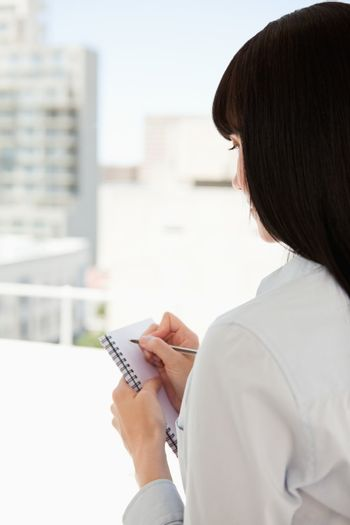 A woman with her back turned begins to write down some informati