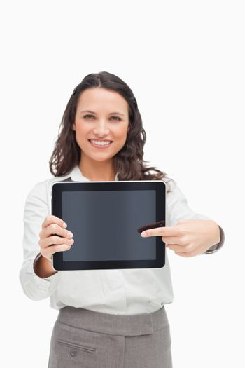 Portrait of a brunette showing and pointing a touchpad screen