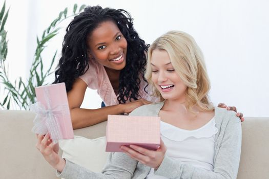 A woman opens a box containing a present and her friend smiles