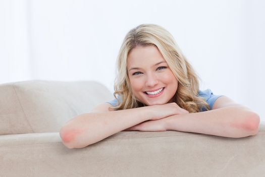 A smiling woman is resting her chin on her hands