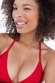 Happy woman in bikini blinking an eye