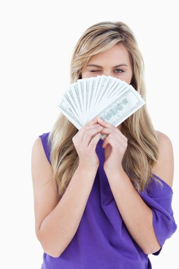 Blonde woman blinking an eye while holding bank notes