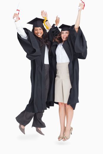 A full length shot of two women jumping in celebration after graduating