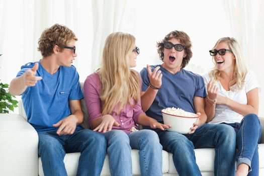 Friends laugh and joke around while watching a movie
