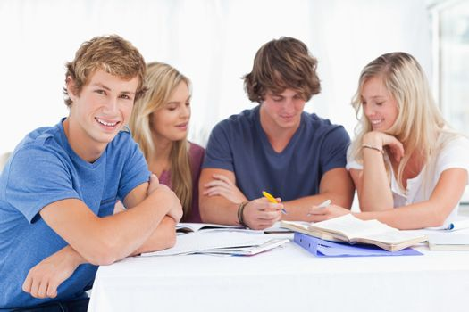 A group of students sitting together as they all study as one si