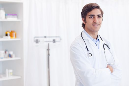 Smiling doctor standing in examination room