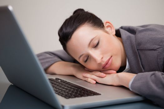 Businesswoman taking a nap on her laptop