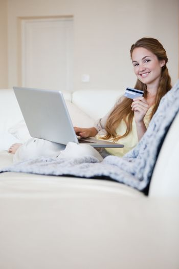 Woman on the sofa booking a flight online