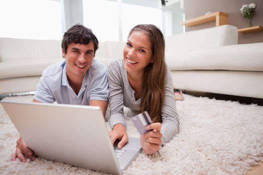 Couple lying on the floor booking holidays online