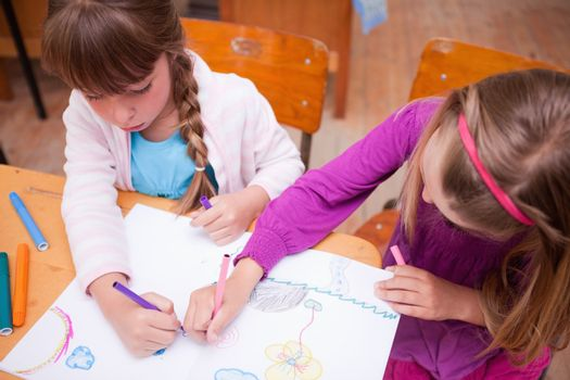 Schoolgirls drawing in a coloring book