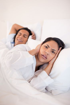 Woman being annoyed by snoring boyfriend