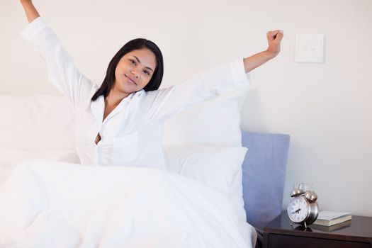 Woman stretching on her bed to wake up
