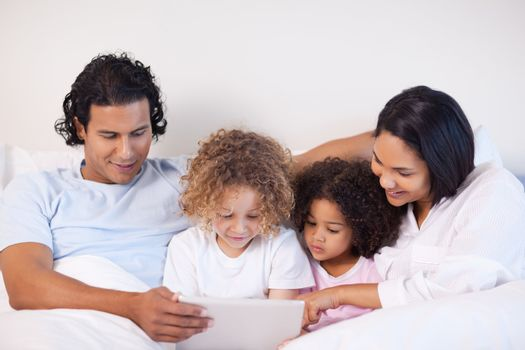 Family sitting on the bed surfing the web