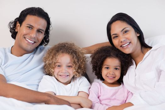 Smiling family sitting on the bed together