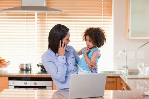 Mother and daughter with cellphone and notebook in the kitchen t