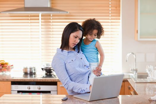 Mother and daughter using laptop in the kitchen together