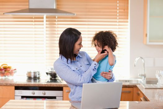 Mother and daughter using laptop and cellphone in the kitchen to